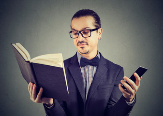 Smart man with phone reading book