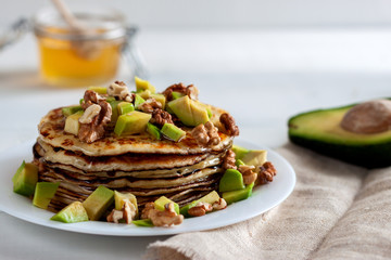 On the table there is a dish with pancakes, honey and nuts.