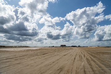 Cloudy sky over the broad sand road in Sankt Peter Ording, Germany at the Northern Sea coast.