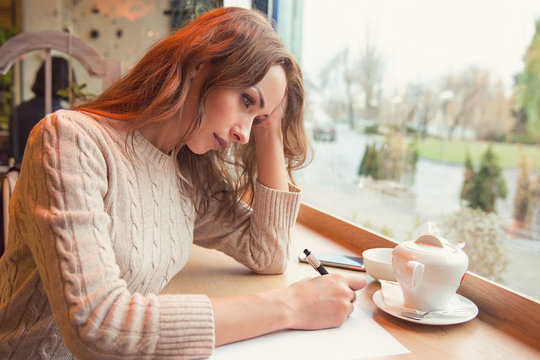 Sad young woman writing letter with broken heart