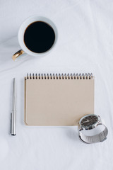 Cup coffee , notebook with pen,  clock, candle on bed, top view. Women clothing. Flat lay, cozy concept