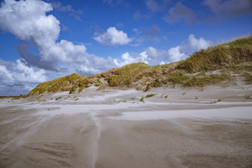 Grass covered dunes at the white sand beach of the Northern Sea in Sankt Peter Ording, Germany with a cloudy blue sky in the background.