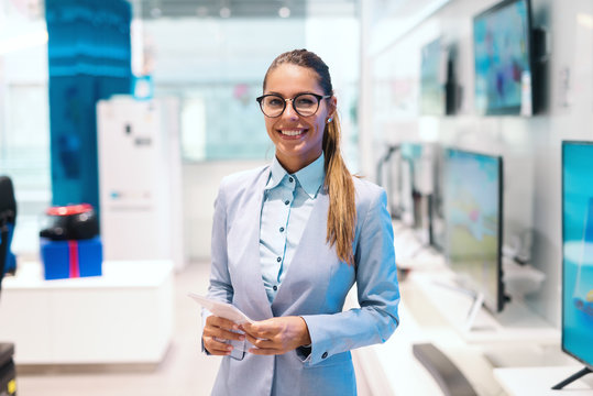 Beautiful smiling Caucasian woman dressed in suit standing in tech store and looking at camera.