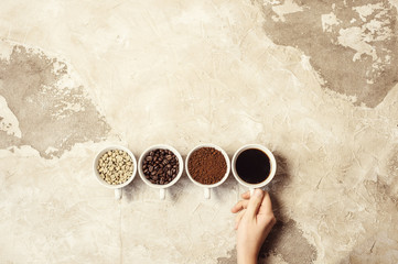 four types of coffee unroasted, bean, ground and one in cup