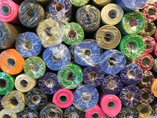 Rolls of textured decorative wrapping paper of different colors on the shelf in the store