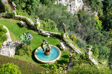 Beautiful traditional garden with dolphins statue playing inside artistic fountain in Eze village on Franch Riviera