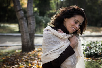Charming middle aged woman feeling cozy wrapped in white shawl at park during fall season. Beautiful mature lady feeling warm in nature outdoors