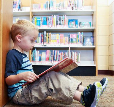 Preschool child reading a book at the library