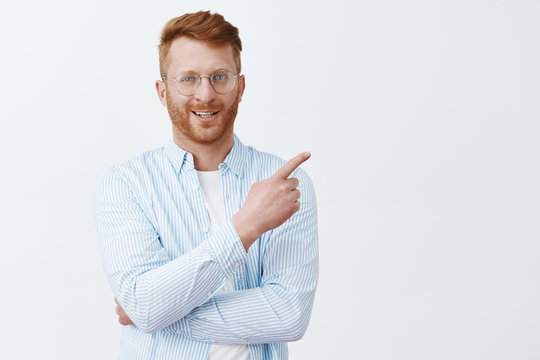 Indoor shot of good-looking confident and bossy male entrepreneur in shirt and glasses with red hair, pointing at upper right corner and smirking, knowing what is good for business, giving good advice