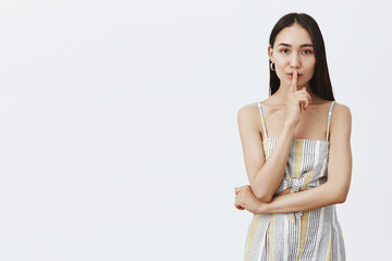 Girl sharing her secrets of beauty. Portrait of charming sensual and fashionable woman in matching top and shorts, saying shh while showing shush gesture with index finger over mouth