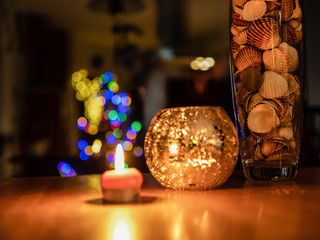 The vase with sea shells near candle and nice blur Christmas lighting