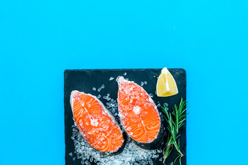 Raw salmon fish on black plates for cooking steaks on blue restaurant kitchen background top view space for text
