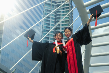 Asian female graduated students raise hand with cap up to celebrate the success
