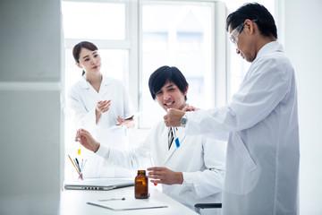 科学者三人で実験に取り組んでいる風景