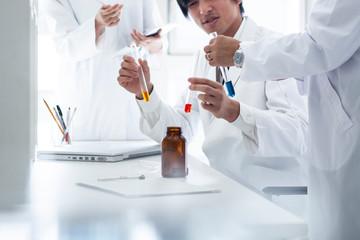 研究員たちは試験管を見比べ実験を行っている