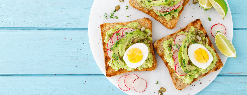 Toasts with avocado guacamole, fresh radish, boiled egg, chia and pumpkin seeds. Diet breakfast. Delicious and healthy plant-based food. Flat lay. Top view. Banner