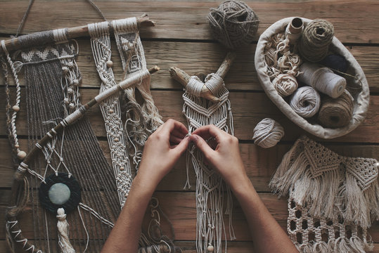 Female hands weaving macrame on a wooden table. Do it yourself. Top view.