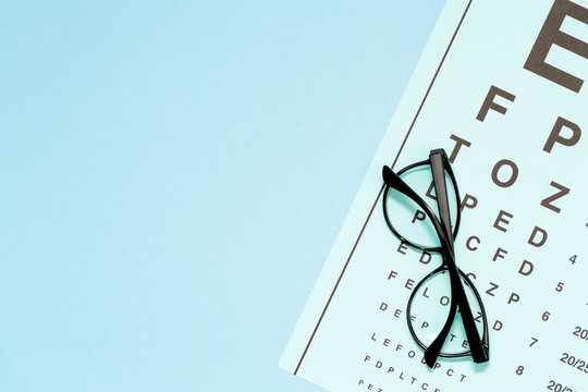 Eye test, eye examination. Glasses with transparent optical lenses on eye test chart on blue background top view