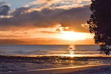 A peaceful sun sets on the beach landscape at Gisborne, New Zealand.