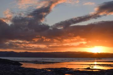 The orange sunset and stirking cloud formations impress above Gisborne, New Zealand.