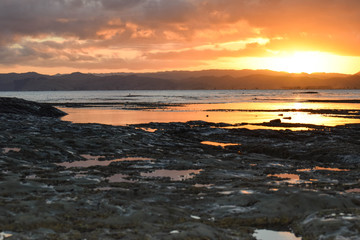 The still rock pools reflect the sunset sky in Gisborne, New Zealand.