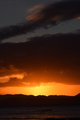 A bright orange sunset nestled between a dark sky and the black hillside in Gisborne, New Zealand.