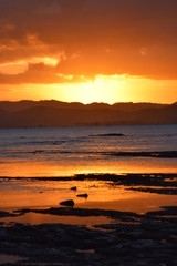 A bright sun setting above the dark hills reflected in the beach shallows at Gisborne, New Zealand.