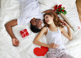 Valentine's Day. happy couple  with red hert and flowers in bed