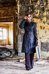 Girl in a black cloak, a scarf and a diplomat in an abandoned house. A spy in a secret meeting