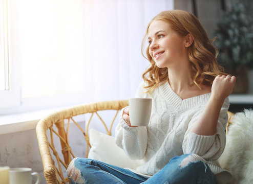 happy young woman drinking morning coffee by window in winter