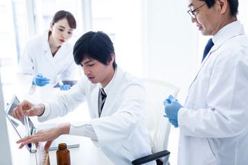 スポイトを用いて実験を行う科学者たち