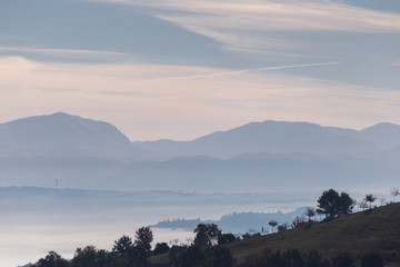 Fog filling a valley in Umbria (Italy), with layers of mountains and hills, trees in the foreground and various shades of blue