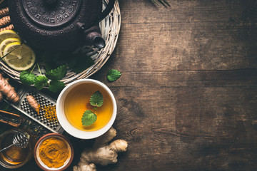 Herbal turmeric tea background. Cup of healthy turmeric spice tea with iron teapot and ingredients:  lemon,  ginger, cinnamon sticks and honey , top view with copy space. Immune boosting remedy