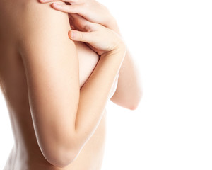 Cropped photo of a young woman's breast. Naked young woman is covering her breast by hands. Isolated over white