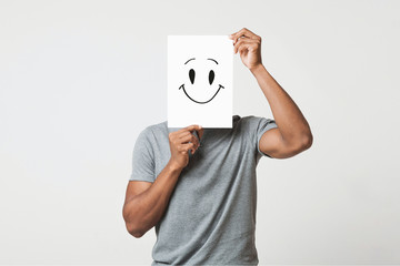 Black man holding paper with smiley face