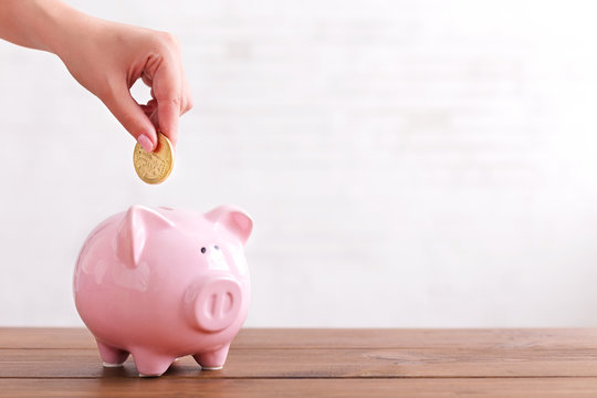 Hand put coin into pink color piggy bank