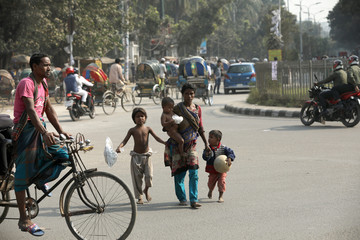 Woman holds her children as they cross a road in Dhaka