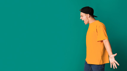 Furious teen guy shouting over turquoise background