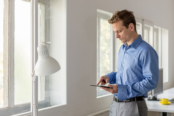 Young businessman browsing the internet on digital tablet