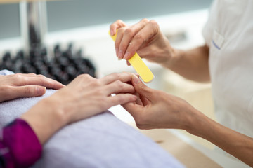 Manicurist shaping the nails with a file