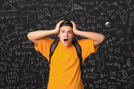 Shocked student standing by blackboard with math formulas