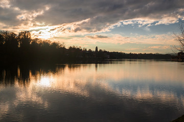 Panoramic view of the Ticino river with clouds and trees that are reflected in its clear water, on a winter day at sunset.