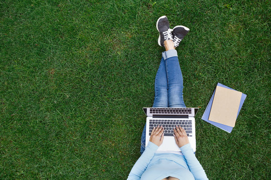 Top view of woman sitting in park on the green grass with laptop