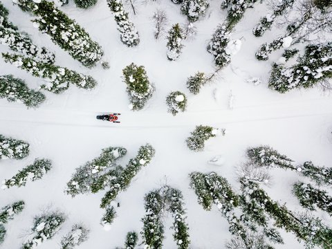 Aerial view of snowmobile in snow winter day in rural Finland