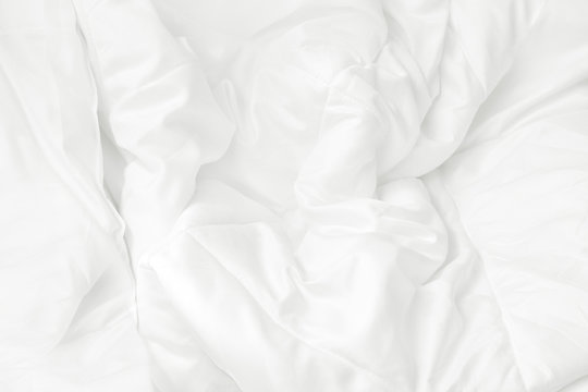 Close up top view of white bedding sheet and wrinkle messy blanket in bedroom after wake up in the morning.