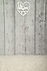 White wooden floor background with white sheepskin and white Christmas decoration