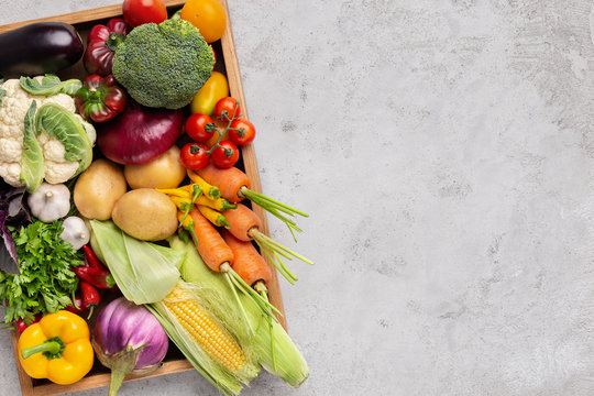 Fresh organic vegetables in wooden box on gray