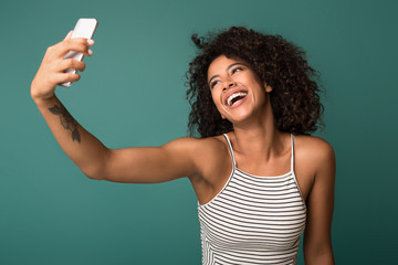 Laughing african-american woman taking selfie on background