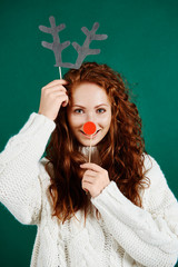Woman in christmas mask on green background
