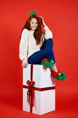 Happy woman sitting on big christmas present